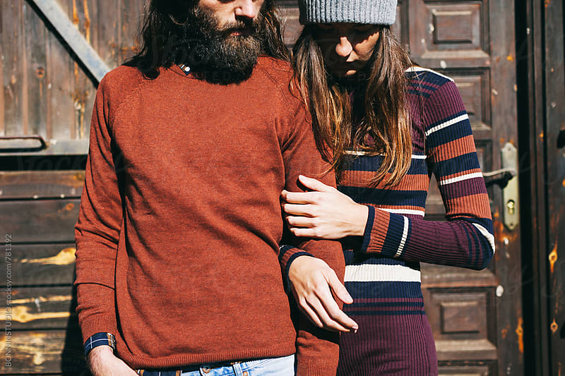 Portrait of hipster couple standing in front of a wooden cabin. by BONNINSTUDIO for Stocksy United