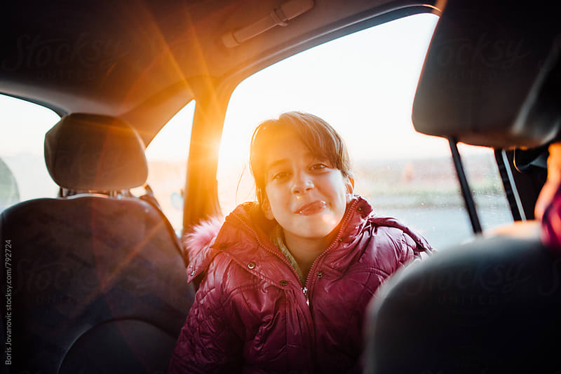 Young girl mocking in the car by Boris Jovanovic for Stocksy United