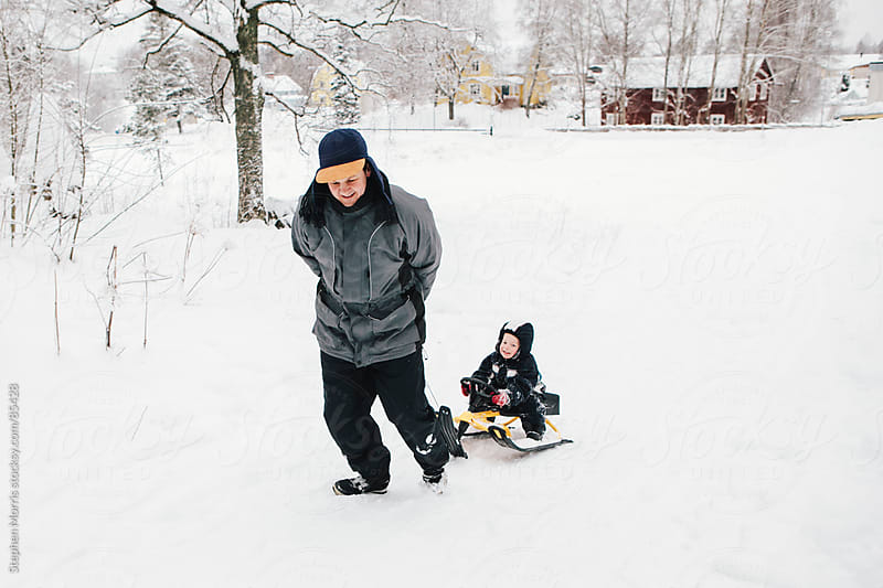 Father Pulling Son on Sled in Snow by Stephen Morris for Stocksy United