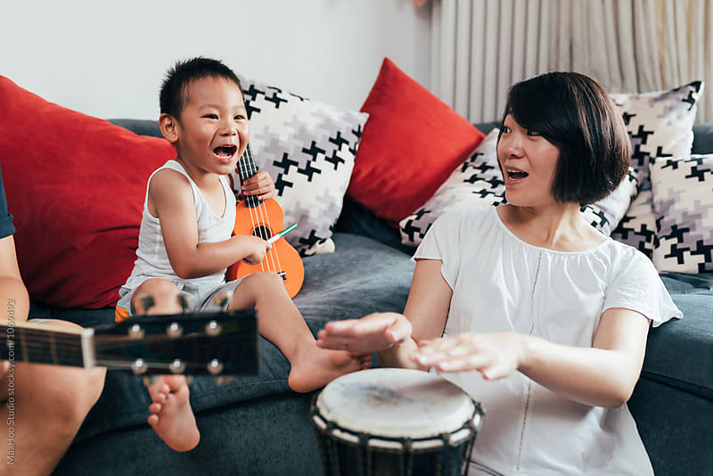 Father,pregnant mother and son playing instruments at home by MaaHoo Studio for Stocksy United