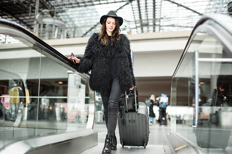 Attractive young woman in black on the escalator by Irina Efremova for Stocksy United