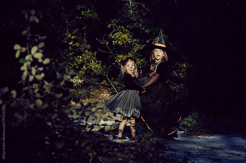 2 surprised girls dressed up as a Witch and a Kitty Cat by Alicja Colon for Stocksy United