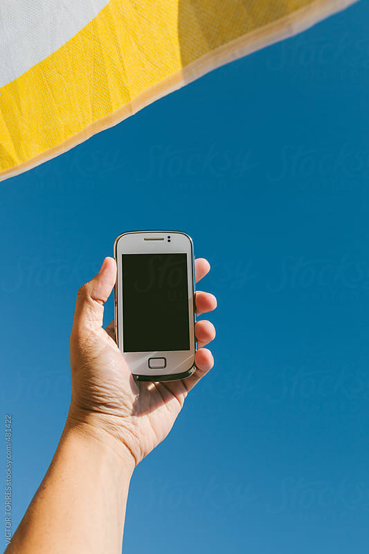 Man Holding a White Mobile Phone Against a Radian Blue Sky by VICTOR TORRES for Stocksy United