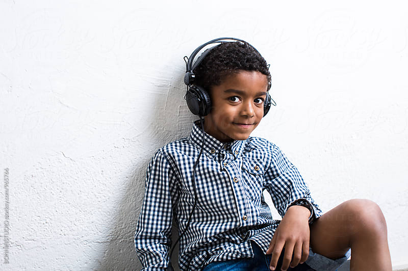 Portrait of a little boy listening music with headphone. by BONNINSTUDIO for Stocksy United