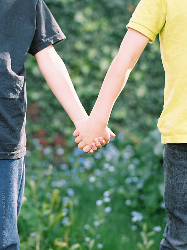 Mid section of two boys holding hands by Kirstin Mckee for Stocksy United