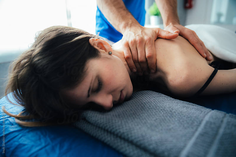 Relaxed young woman lying on her front on a bed receiving a massage on her back by a male therapist by Inuk Studio for Stocksy United