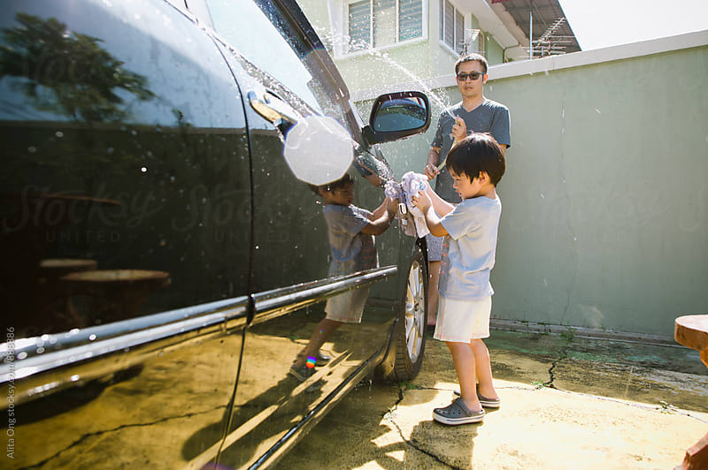 Little boy helping dad with car washing by Alita Ong for Stocksy United