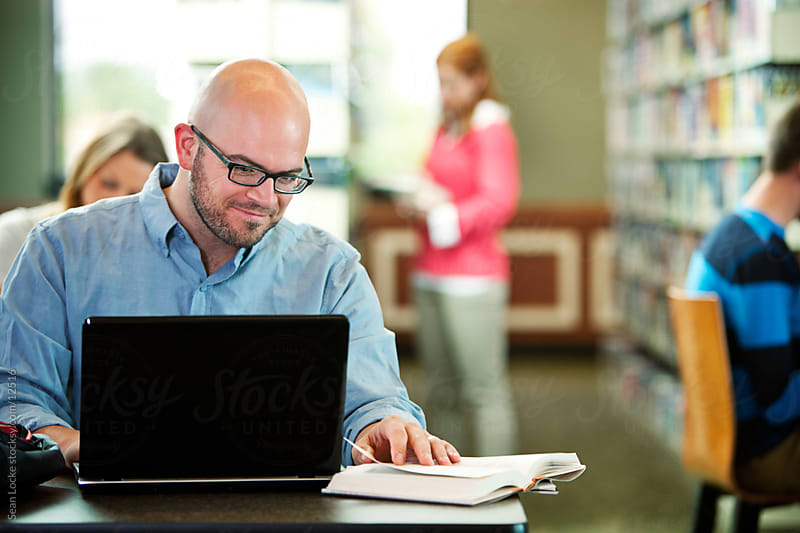 Library: Adult Male Uses Laptop in Library by Sean Locke for Stocksy United