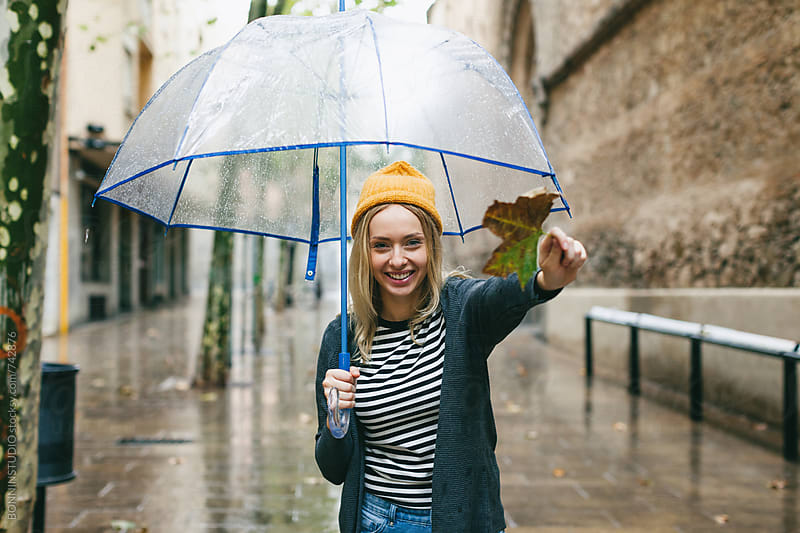 Woman showing a leaf on the street in a rainy day. by BONNINSTUDIO for Stocksy United