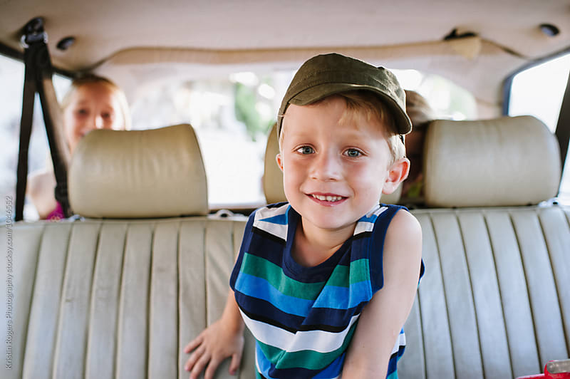 Young cute boy smiling sitting in backseat of car by Kristin Rogers Photography for Stocksy United