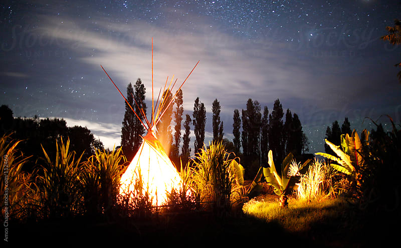 Fire inside a teepee by Amos Chapple for Stocksy United