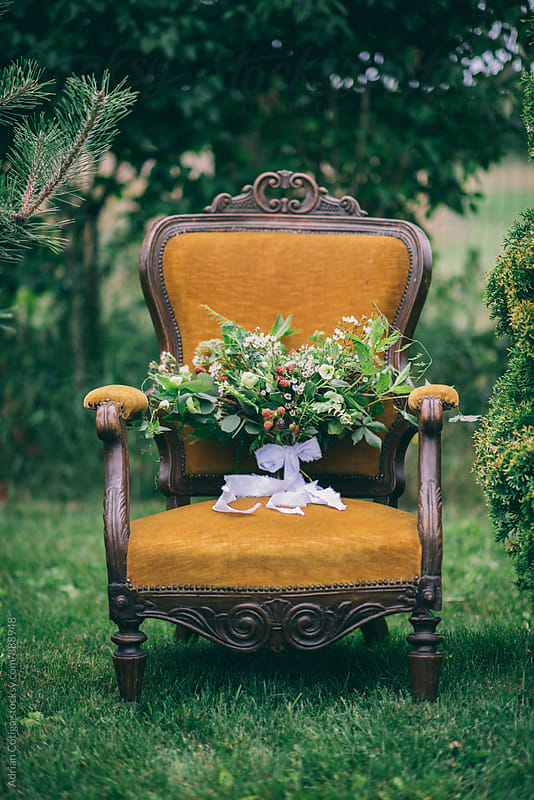 Sauvage wedding bouquet on a vintage old chair; Bridal bouquet by Adrian Cotiga for Stocksy United