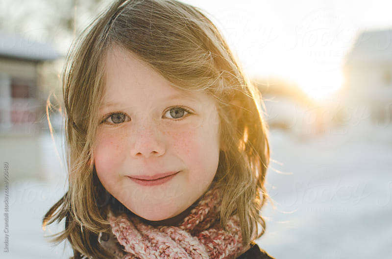 Child smiling on a snowy day by Lindsay Crandall for Stocksy United