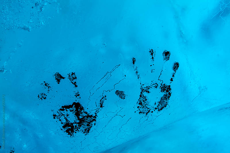 Muddy handprints on blue ice in a glacier ice cave by Mihael Blikshteyn for Stocksy United