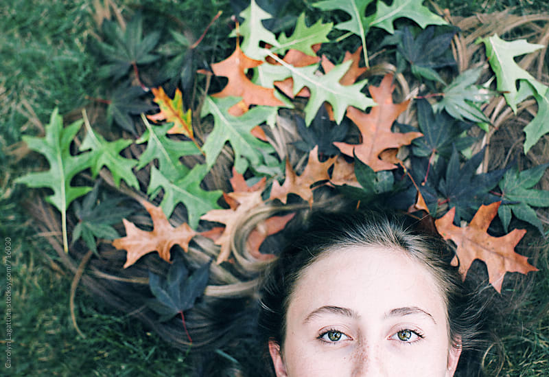 Partial portrait of a teenage girl whose hair is decorated with multi-colored fallen leaves by Carolyn Lagattuta for Stocksy United