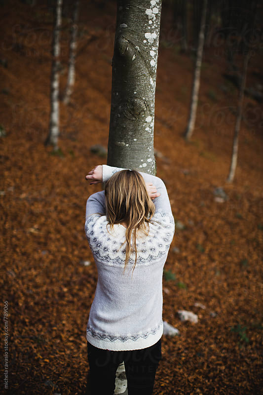 Young woman leaning against a tree in the woods by michela ravasio for Stocksy United