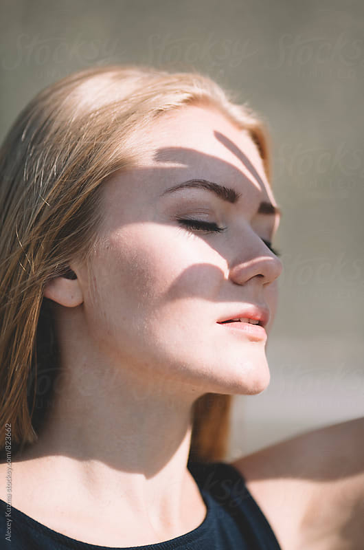 Portrait of young blond woman with shadow on her face  by Vesna for Stocksy United