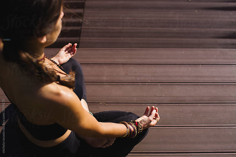 Woman doing lotus pose outdoors by michela ravasio for Stocksy United