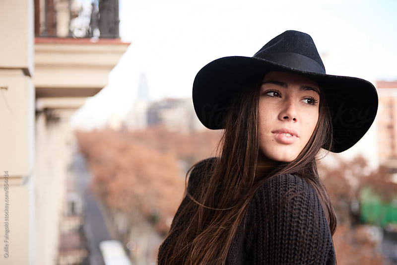 Young woman in black hat looking away by Guille Faingold for Stocksy United