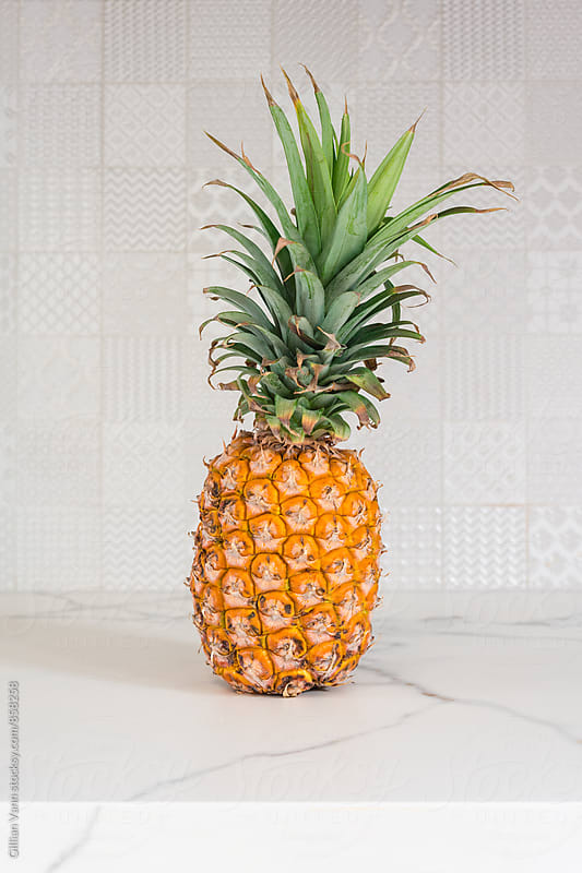 pineapple on a white countertop, with patterned tile background by Gillian Vann for Stocksy United