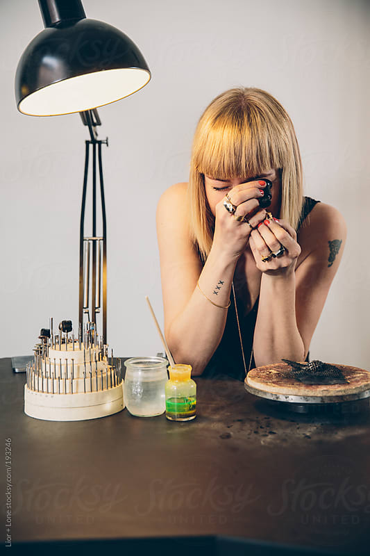 Young attractive jewelry designer evaluating a ring in her studio by Lior + Lone for Stocksy United