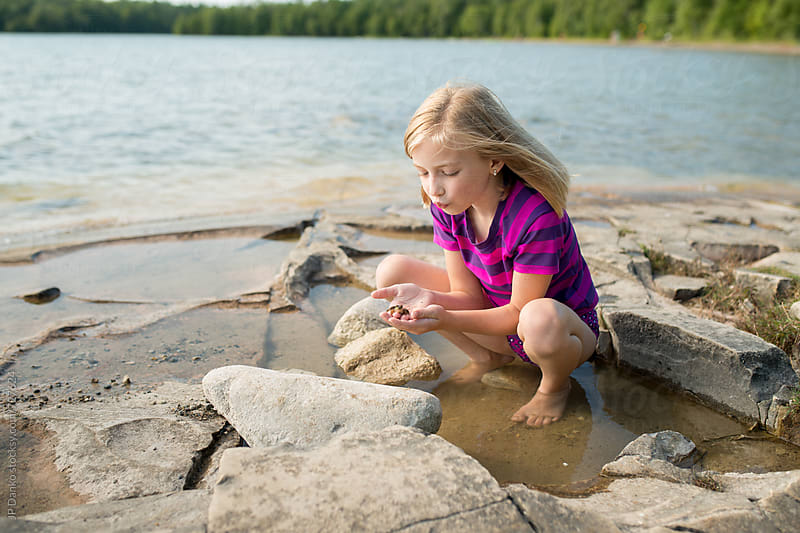 Little Girl Playing With Frogs on a Rocky Northern Cottage Lakeshore on Warm Sunny Summer Day by JP Danko for Stocksy United