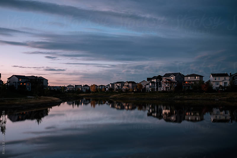 Homes back onto a still pond at dusk by Riley J.B. for Stocksy United