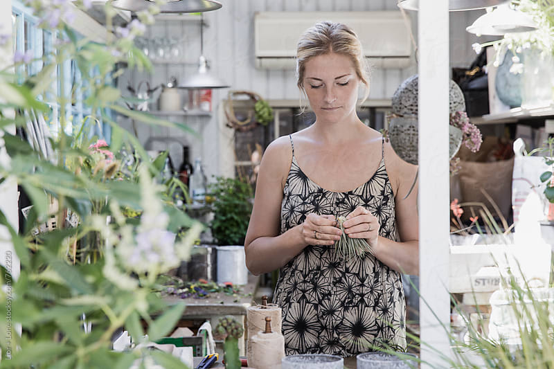 Young woman trimming a plant in a flower shop by Lior + Lone for Stocksy United