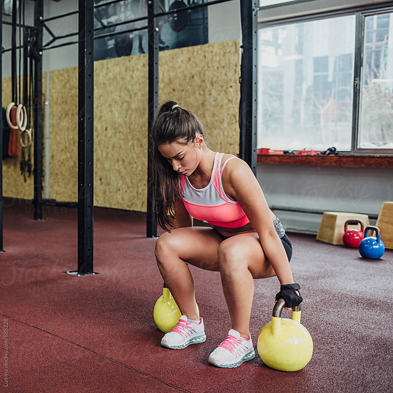 Woman Lifting a Kettle Bell  by Lumina for Stocksy United