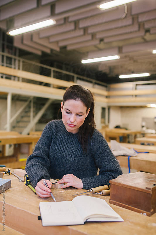 Female woodworker working behind a workbench and looking at her notebook for notes by Ivo de Bruijn for Stocksy United