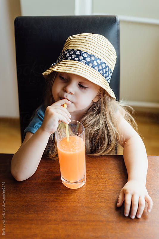 Beautiful child drinking a healthy juice by Boris Jovanovic for Stocksy United