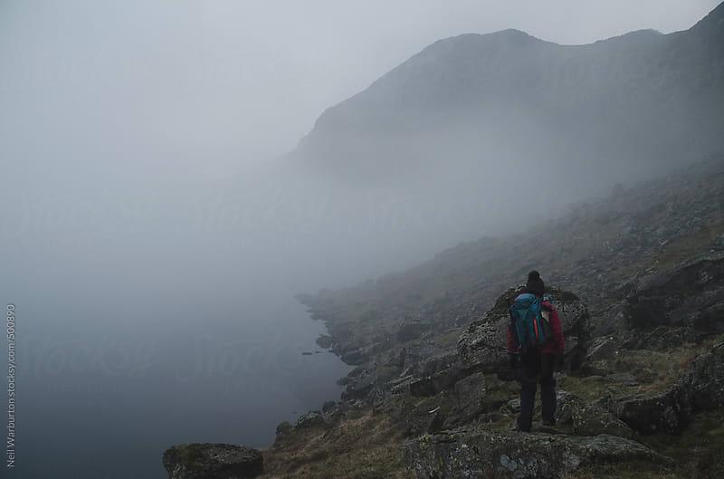 Hiker in misty mountain landscape by Neil Warburton for Stocksy United