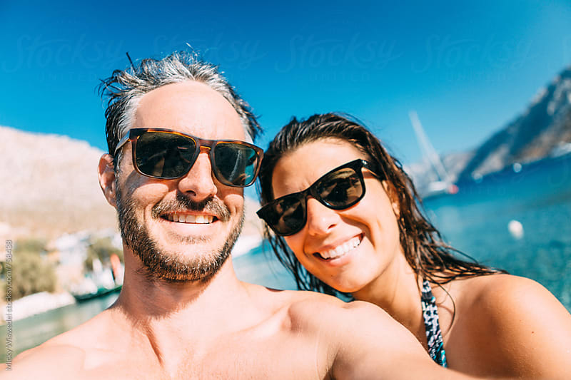 couple with sunglasses taking a selfie at the beach on a summers day by Micky Wiswedel for Stocksy United