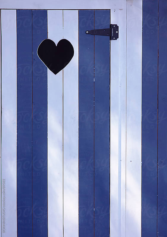 Blue and white door with hole wiht a form of heart. by BONNINSTUDIO for Stocksy United