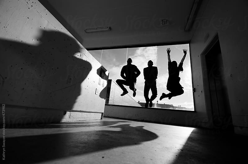 Three people jump in the stairwell of a parking garage, backlit by a bright window by Kathryn Swayze for Stocksy United