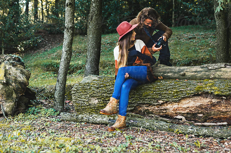 Man showing his photos to the woman in the woods. by BONNINSTUDIO for Stocksy United