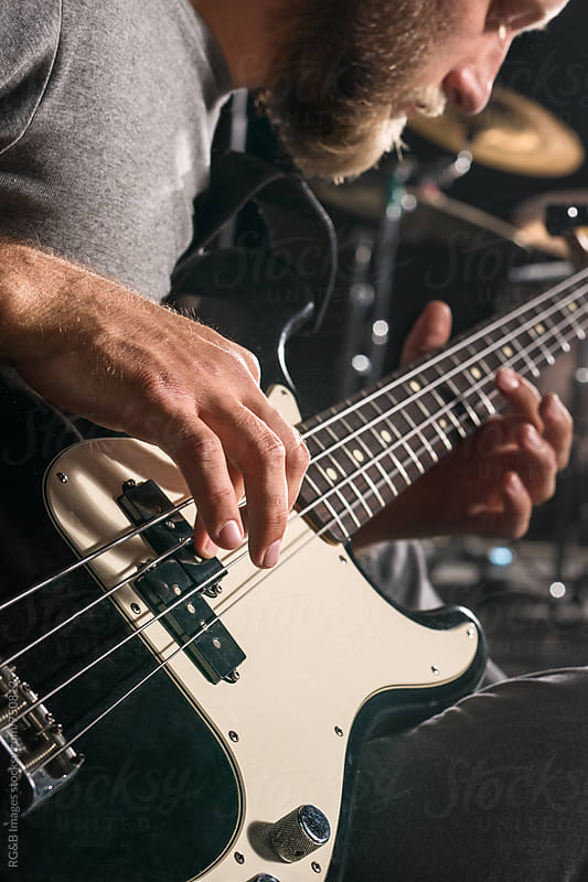 Closeup of a man playing an electrig bass guitar by RG&B Images for Stocksy United