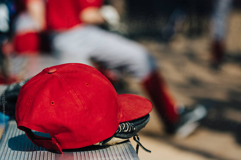 Red baseball cap on a bench at a game by Gabriel (Gabi) Bucataru for Stocksy United