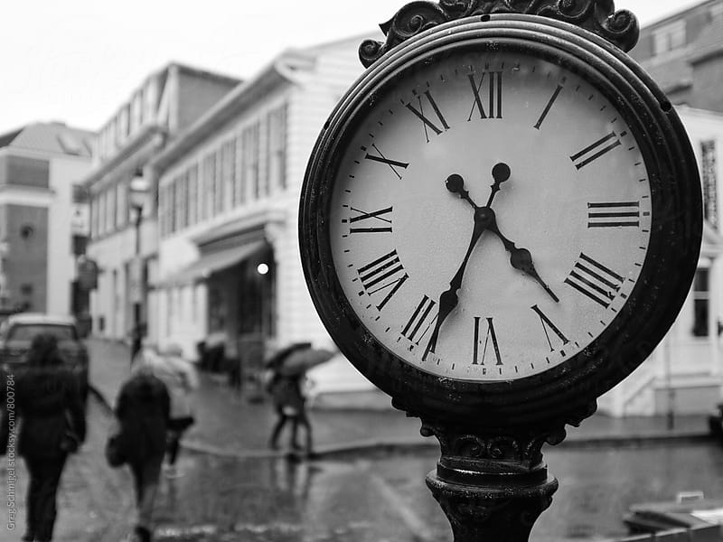 Black and white street photo of people walking in the rain in the city and a big public clock by Greg Schmigel for Stocksy United
