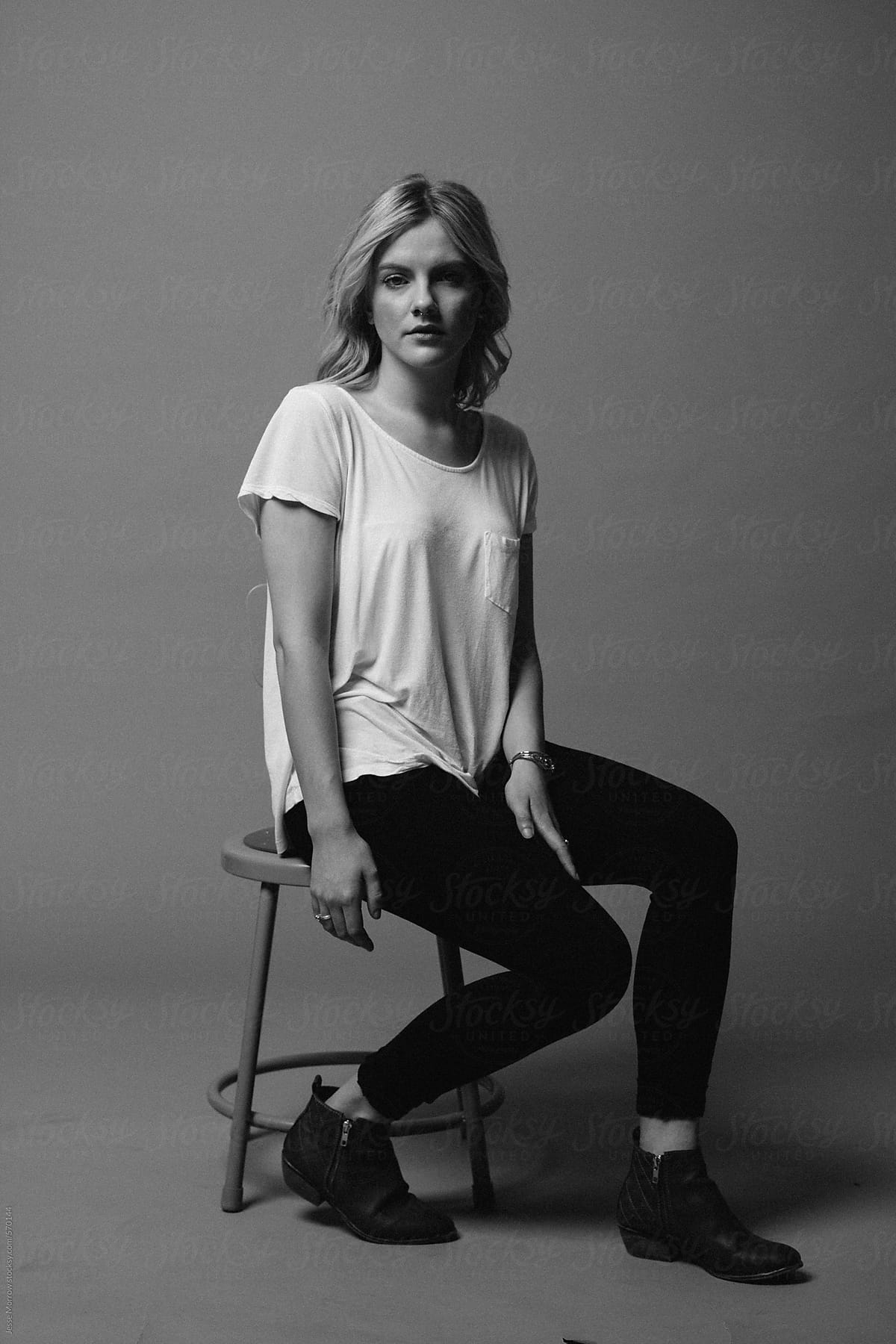 Black and white moody portrait of female in studio on stool by jesse morrow for stocksy