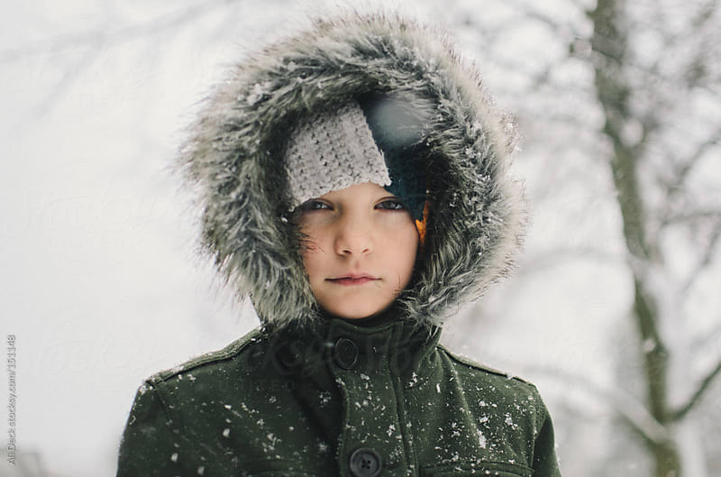 A boy stares in the snow by Ali Deck for Stocksy United