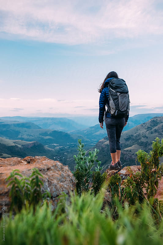 hiker with backpack overlooking a scenic mountainous valley by Micky Wiswedel for Stocksy United