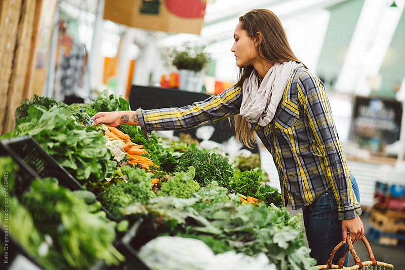 Young attractive woman shops at the farmers market in the Fall by Kate Daigneault for Stocksy United