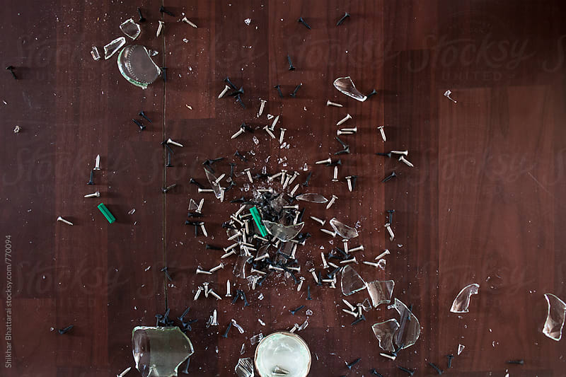 A broken glass container with screws and nails. by Shikhar Bhattarai for Stocksy United