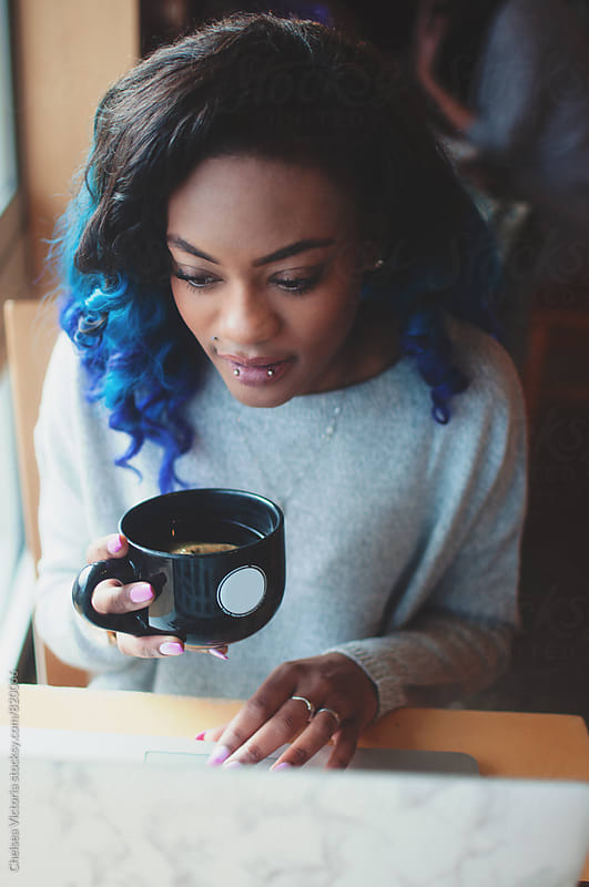 A young african american woman on a laptop at a cafe by Chelsea Victoria for Stocksy United