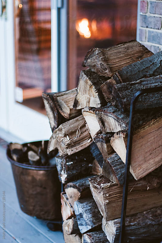 Firewood stacked outside a home with a fire burning inside. by Holly Clark for Stocksy United