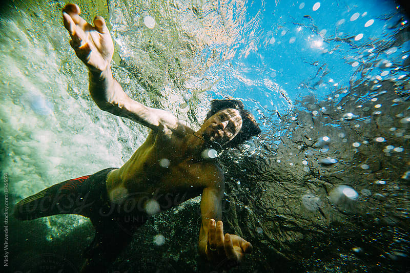 Man diving under the waters surface in a mountain river by Micky Wiswedel for Stocksy United