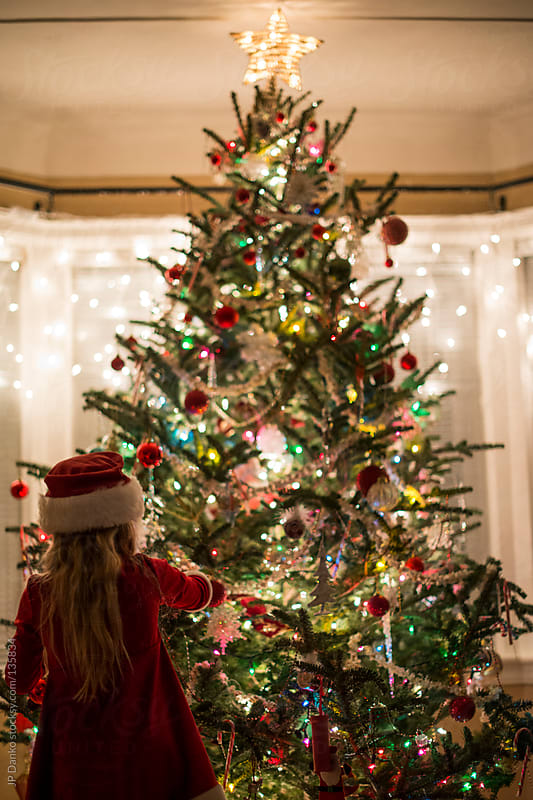 Little Girl Decorating Christmas Tree with Ornaments by JP Danko for Stocksy United