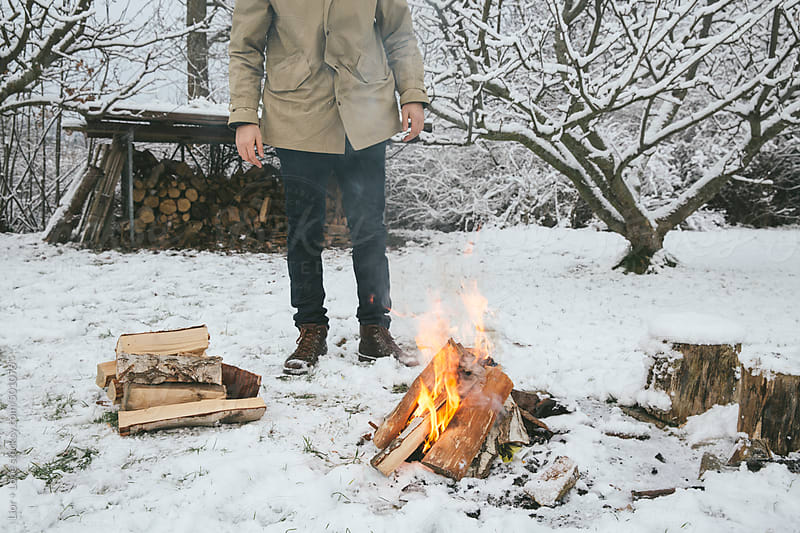 Man warming up next to a bonfire in the snow by Lior + Lone for Stocksy United
