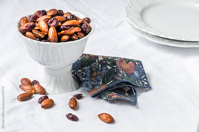 Almonds and Dried Cranberries in a footed white serving bowl by Rhonda Adkins for Stocksy United